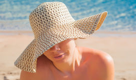 Young woman in a straw broad-brimmed hat, part of the face cover Stock Photography
