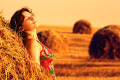 Young woman in straw field with bales. Day dreaming with closed eyes. Royalty Free Stock Images