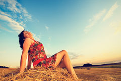 Young woman in straw field with bales. Day dreaming with closed eyes. Stock Photos