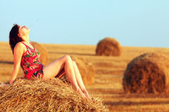 Young woman in straw field with bales. Day dreaming with closed eyes. Stock Images