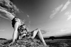 Young woman in straw field with bales. Day dreaming with closed eyes. Stock Image