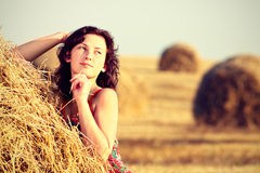 Young woman in straw field with bales. Dreamily looking away Royalty Free Stock Images
