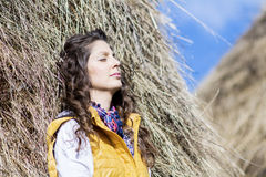 Young woman in straw field with bales. dreaming with closed eyes. Royalty Free Stock Images
