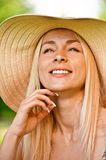 Young woman in straw hat. Cheerfully laughs Stock Photography