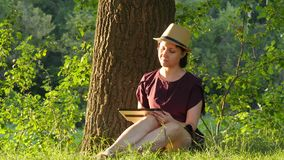 A young woman in a straw hat and dress is sitting near a tree and using a tablet computer. Girl chatting or reading a book. 4k stock video footage