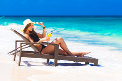 Young woman in straw hat laying at the tropical beach and enjoying cocktail royalty free stock image