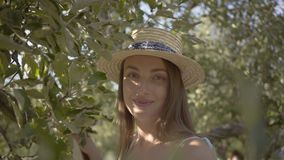 Young woman in straw hat looking at the camera standing on a ladder in the green summer garden. Harvest time, rural. Lifestyle stock footage