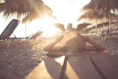 Young woman in straw hat sitting on a tropical beach,enjoying sand and sunset.Laying in the shade of palm tree parasols. Summer vacation concept Stock Image