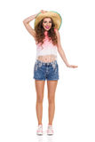 Young Woman in Straw Hat. Smiling young woman in jeans short, pink top and sneakers posing in straw hat. Full length studio shot isolated on white Royalty Free Stock Image