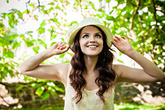 Young woman in straw hat staying in the park Royalty Free Stock Photo