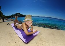 Young woman in straw hat sunbathing on a beach Royalty Free Stock Photo