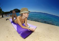 Young woman in straw hat sunbathing on a beach Stock Photo