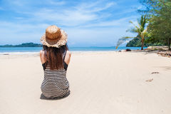 Young woman on tropical beach. Young woman and straw hat on tropical beach royalty free stock photo