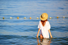 Young woman in straw hat and white tunic in sea water Royalty Free Stock Photography