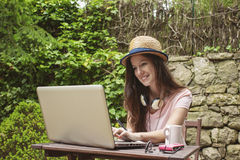 Young woman with straw hat working with laptop in outdoors. Stock Image