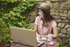 Young woman with straw hat working with laptop in outdoors. Royalty Free Stock Photography