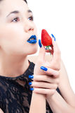 Young woman with strawberry and blue nails. And lips isolated on white background royalty free stock images