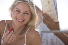 Young woman with strawberry by man with book on sun bed, smiling, portrait Royalty Free Stock Image