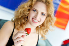 Young woman with strawberry near New car Stock Images
