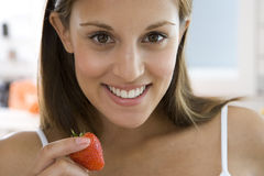 Young woman with strawberry, smiling, portrait Royalty Free Stock Photography