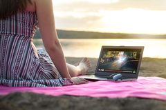Young woman streaming a movie with laptop computer on beach. Young woman streaming a movie with laptop computer on beach at sunset. Watching film stream on royalty free stock image