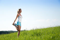 Young woman streching. Young woman is doing fitness exercise in the nature Stock Photo