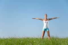 Young woman streching. Young woman is doing fitness exercise in the nature Royalty Free Stock Photo
