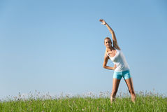 Young woman streching. Young woman is doing fitness exercise in the nature Stock Photography