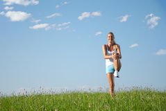 Young woman streching. Young woman is doing fitness exercise in the nature Royalty Free Stock Photos
