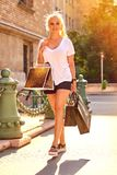 Young woman on the street with bags. A beautiful young blonde woman walking on the sunny street with shopping bags in her armsr Stock Image