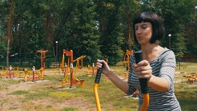 Young Woman on Street Exercise Machines go in for Sports in Slow Motion stock footage