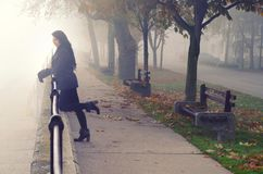 Young woman on the street on foggy autumn day royalty free stock images