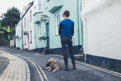 Young woman in street with Leonberger puppy Royalty Free Stock Photo