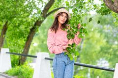 Young woman on the street on a sunny evening. Beautiful girl in jeans, a blouse and small hat is holding a flowering branch and stock image