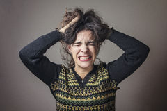 Young woman stressed and angry. Enraged young lady screaming and pulling out her hair Royalty Free Stock Image