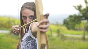 Young woman stretches arrow for bow and aim at the target aimed at the camera stock video footage