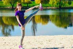 Young woman stretches her leg up . She has is wearing blue sports clothing. The beach and river are in the background. Royalty Free Stock Photo