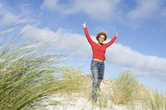 Young woman stretching amongst dunes Stock Photo