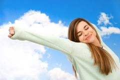 Young woman stretching arms outdoors. Royalty Free Stock Image