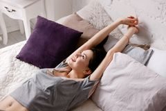 Young woman stretching arms under sunbeams. Past dreams in the morning, calmness and relaxation, staying in bed for a while at holiday concept Royalty Free Stock Photo
