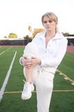 Young woman stretching on athletic field Royalty Free Stock Image