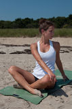 Young Woman Stretching on Beach Stock Image