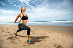 Young woman stretching on beach Stock Images