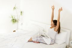 Woman stretching. Young woman stretching in bed while her lap top standing on legs royalty free stock photo