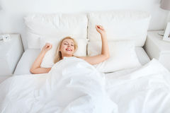 Young woman stretching in bed at home bedroom Stock Images