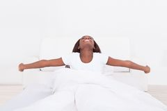 Young woman stretching in bed Royalty Free Stock Photos