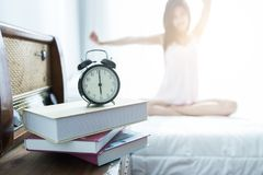 Young Woman stretching on the bed after waking up in the morning. Waking up concept Stock Photos