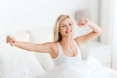 Young woman stretching in bed after waking up Royalty Free Stock Image