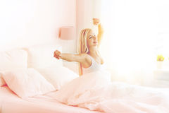 Young woman stretching in bed after waking up Stock Image