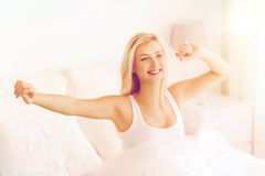 Young woman stretching in bed after waking up Royalty Free Stock Images